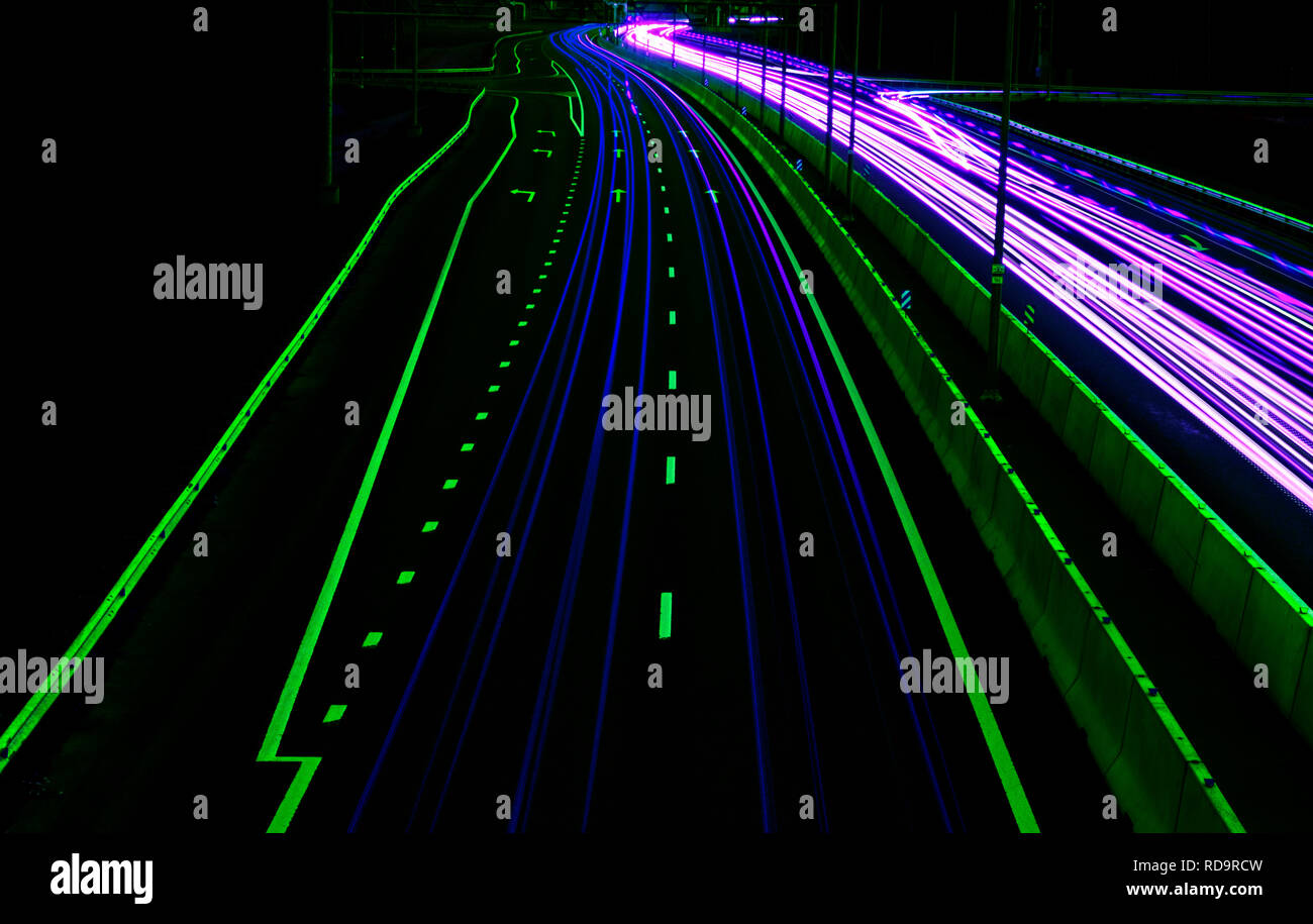 Cars light trails on a curved highway at night. Night traffic trails. Motion blur. Night city road with traffic headlight motion. Cityscape. Light up  - Stock Image