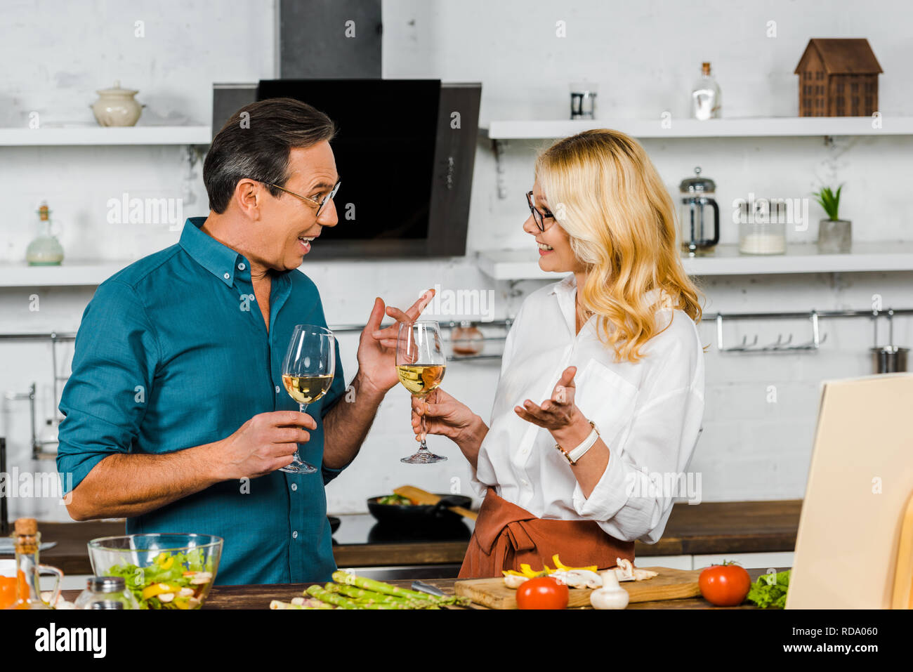 side view of smiling mature wife and husband holding glasses of wine and  talking in kitchen