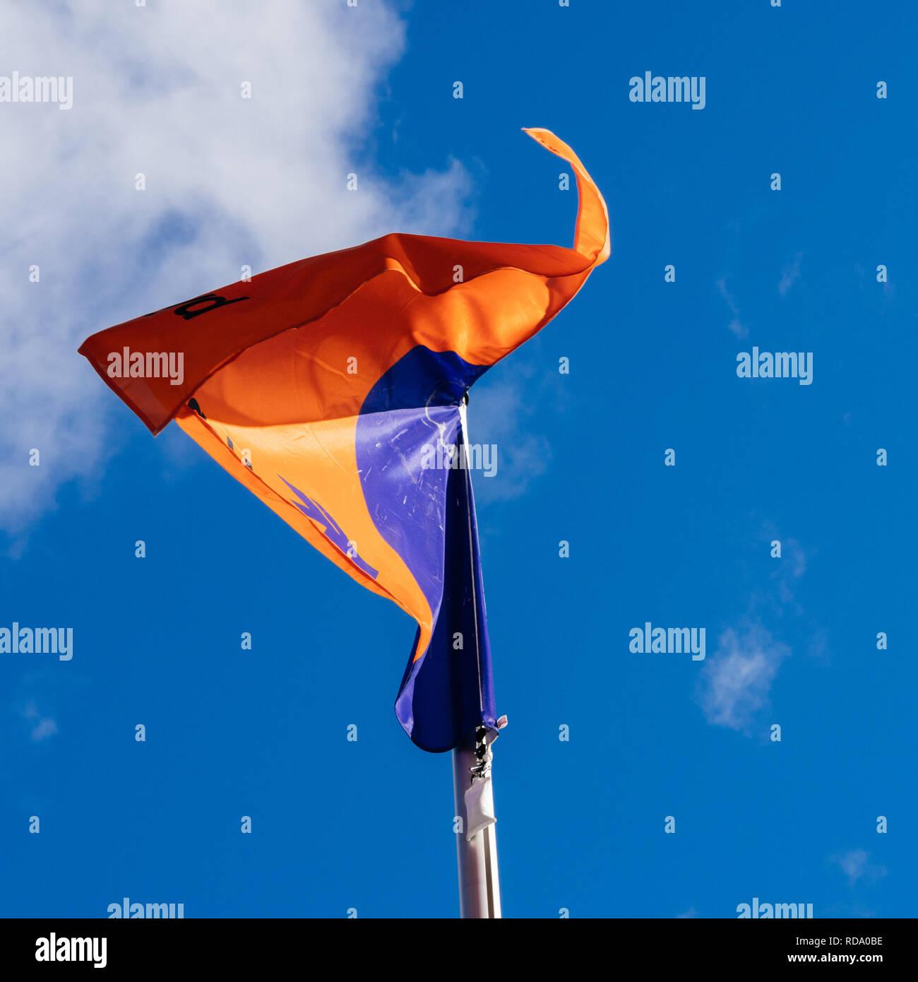 HAMBURG, GERMANY - MAR 20, 2018: Hapag-Lloyd transnational German-based transportation company flag waving against blue sky and white cloud - Stock Image