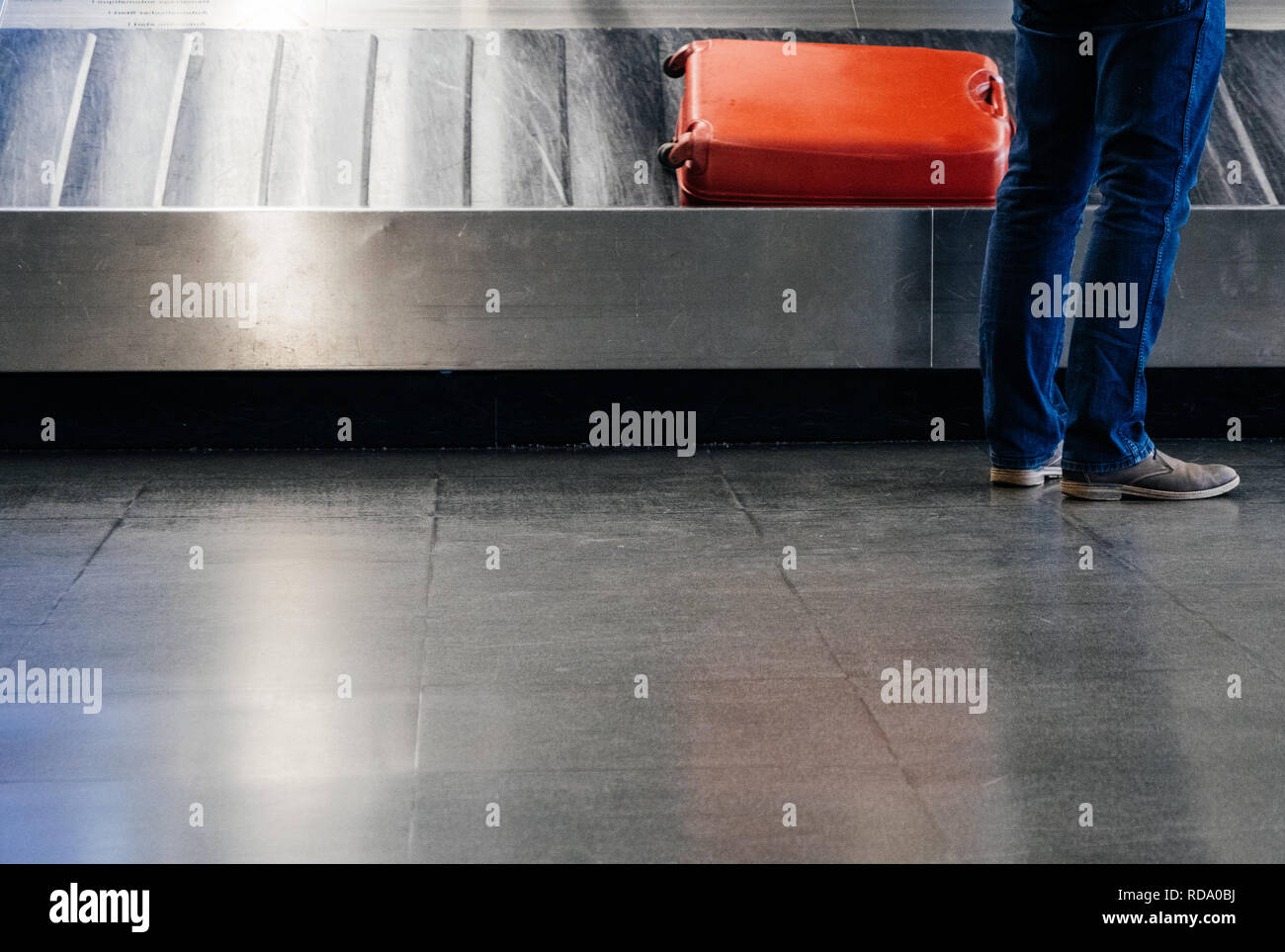 Rear view of a businessman waiting for luggage at the conveyor belt with beautiful red luggage on the belt - Stock Image