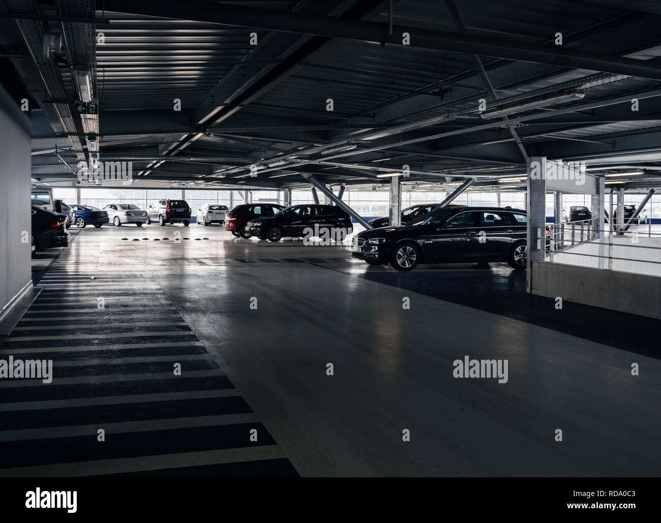 BASEL, SWITZERLAND - MAR 22, 2018: Luxury cars parked inside the parking of a modern airport BMW, MErcedes, Volvo, Saab - Stock Image