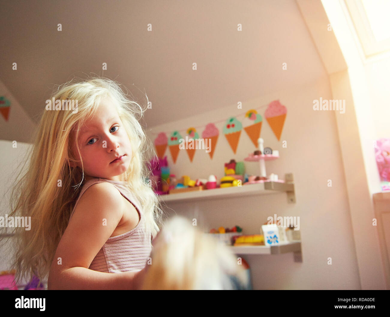 6c1d4a7e218cae Cute little girl holding a toy and looking at camera. Horizontal indoors  shot. -