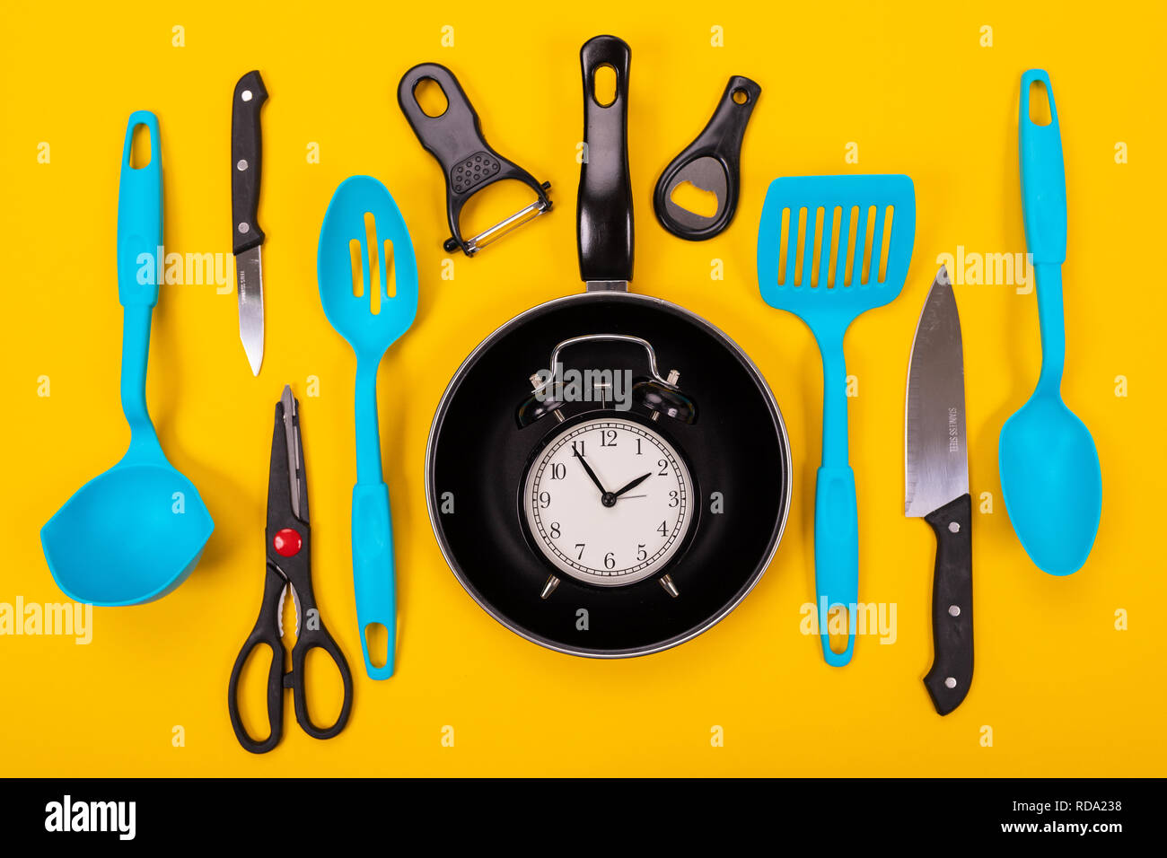 Close up portrait of frying pan with set of kitchen utensils on yellow background Stock Photo