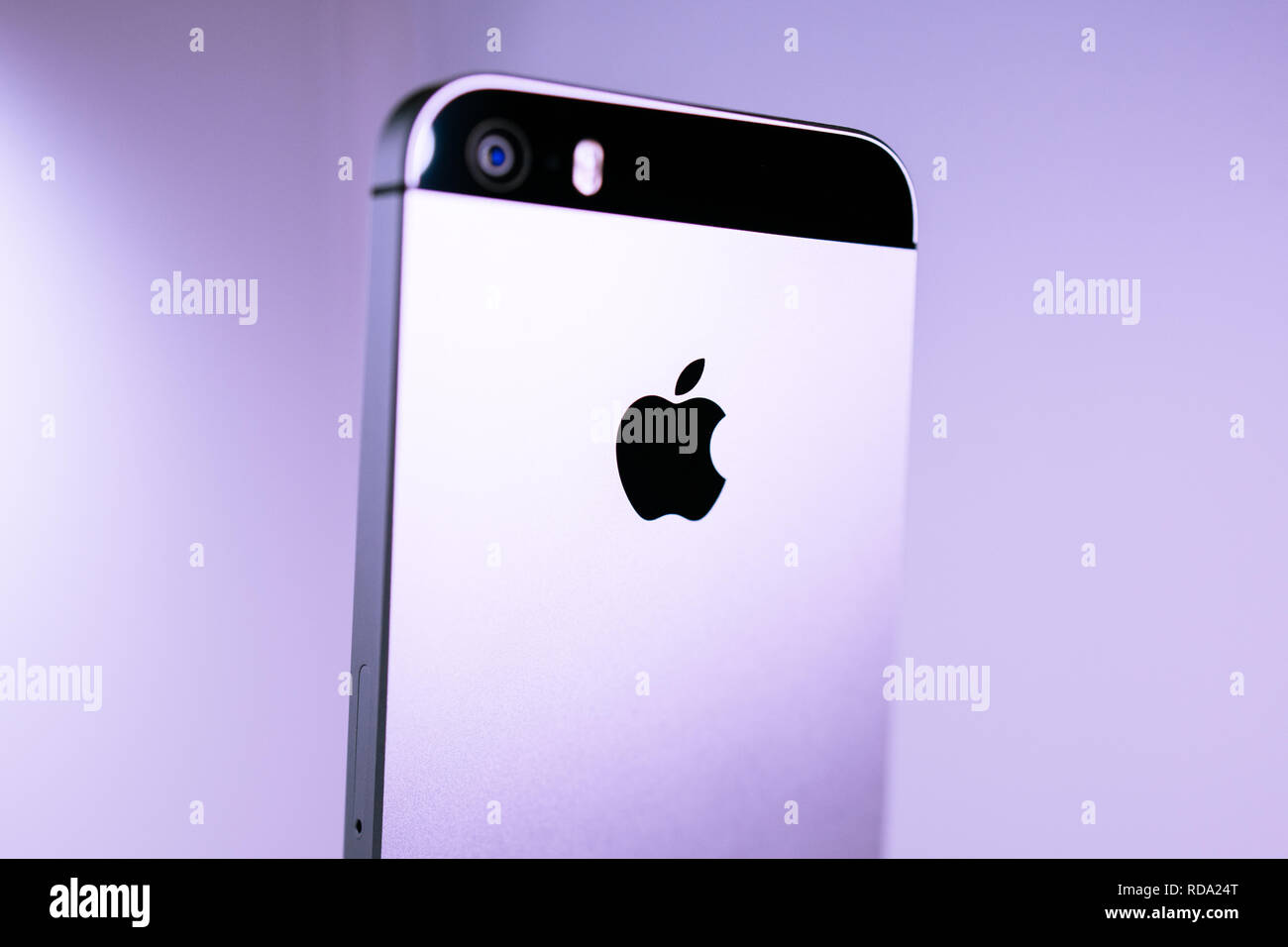 Paris, France - Apr 21, 2016: Newest Apple Computers iPhone SE smartphone after unboxing on pale pink background featuring 12 megapixel camera and Apple logotype - tilt-shift lens used Stock Photo