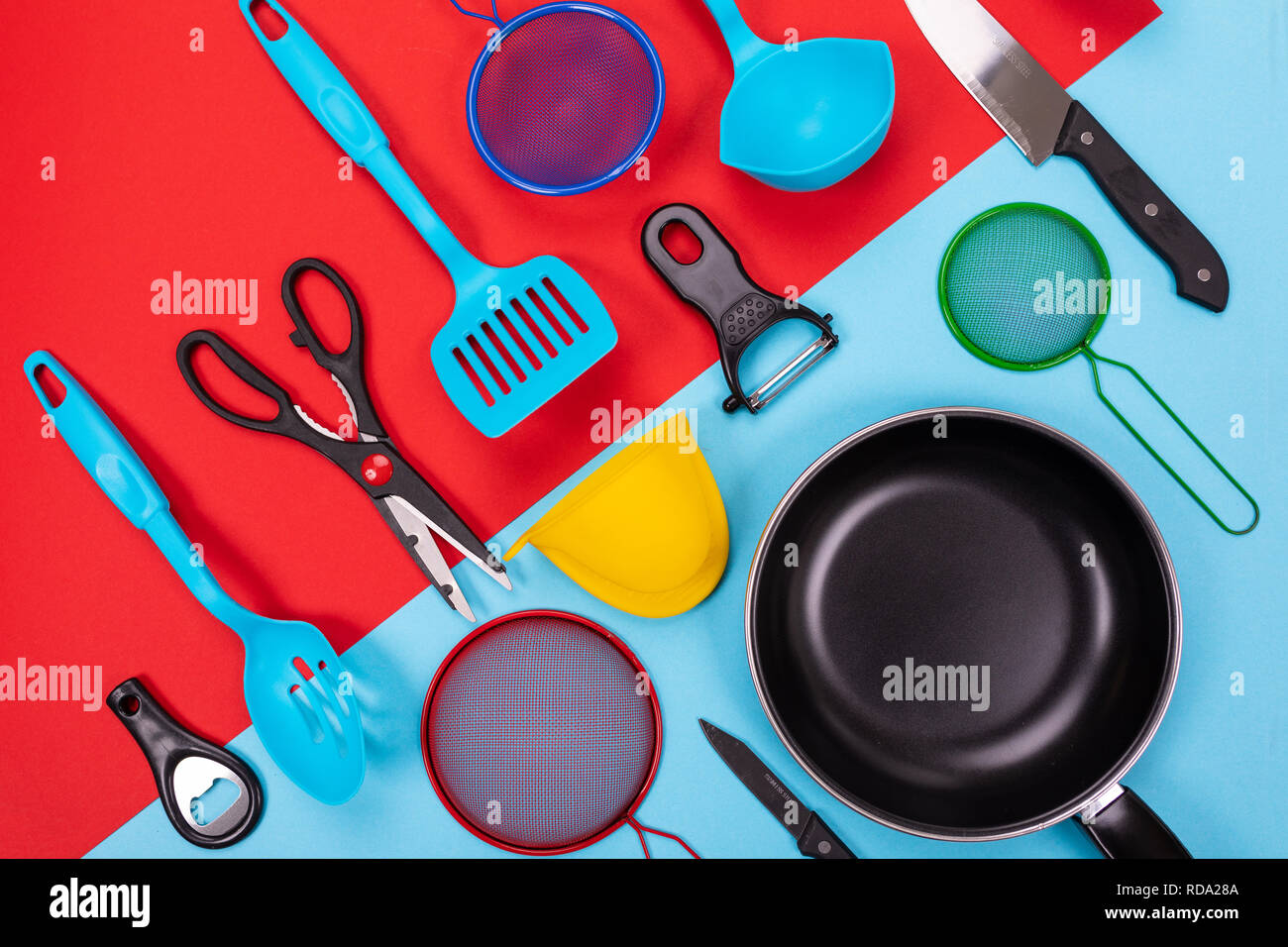 Close up portrait of frying pan with set of kitchen utensils on red-blue background Stock Photo