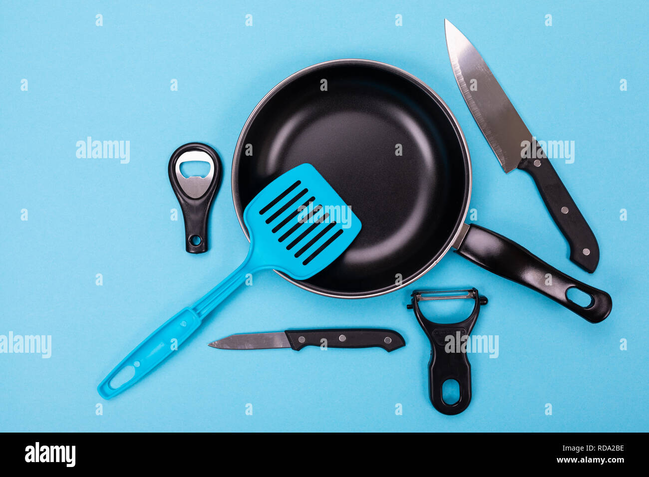 Close up picture of group of kitchen utensils with copyspace on blue background - Stock Image