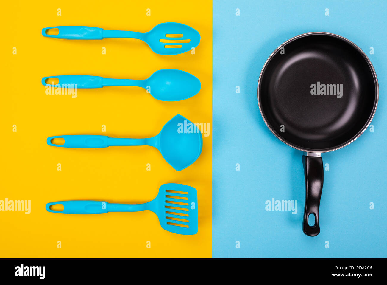 Close-up picture of frying pan with spatula and spoon as kitchen utensils for cooking concept - Stock Image