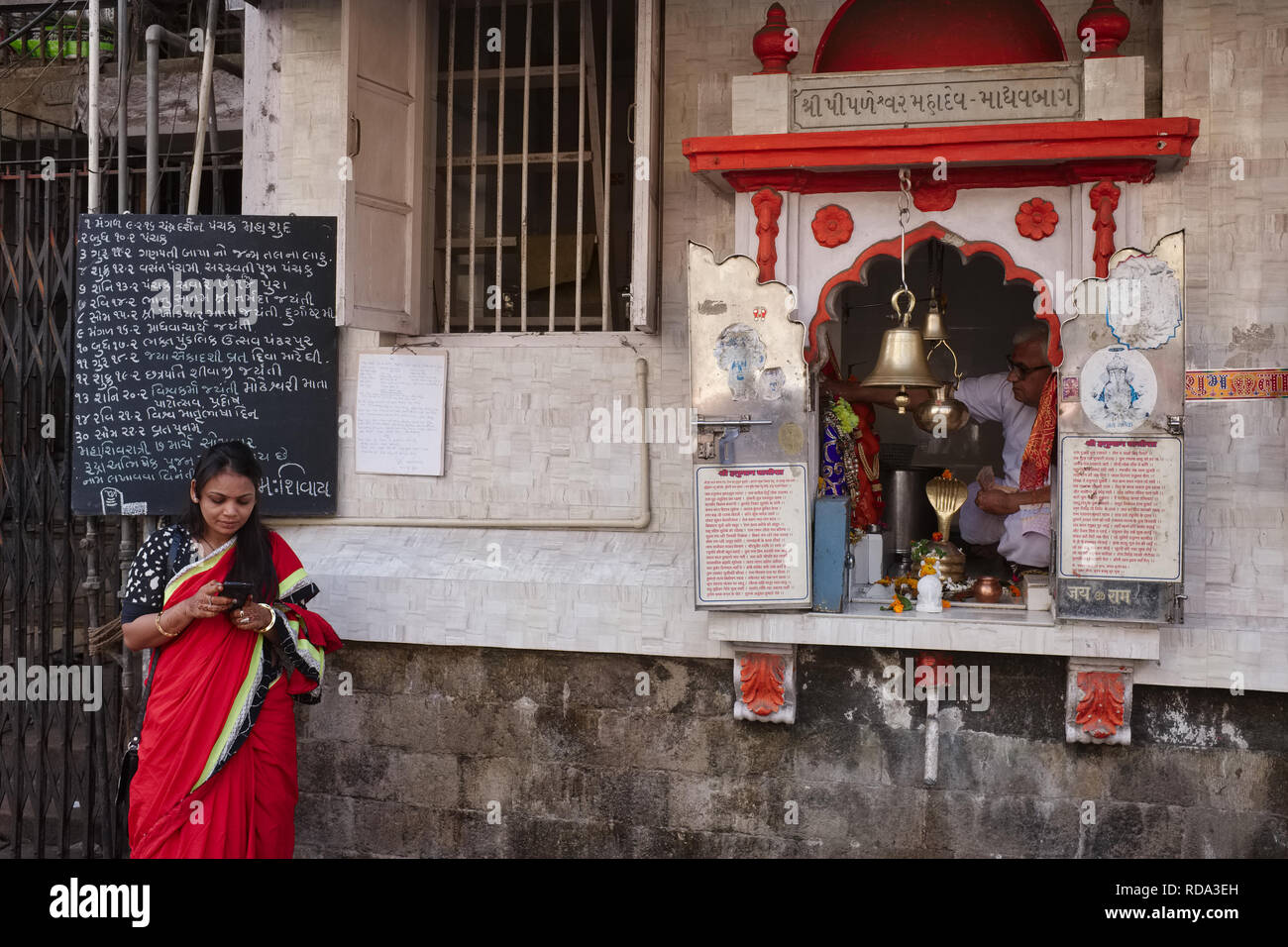 A woman uses her mobile phone, while a priest in his little shrine awaits the next worshipper and donor; Mumbai, India - Stock Image
