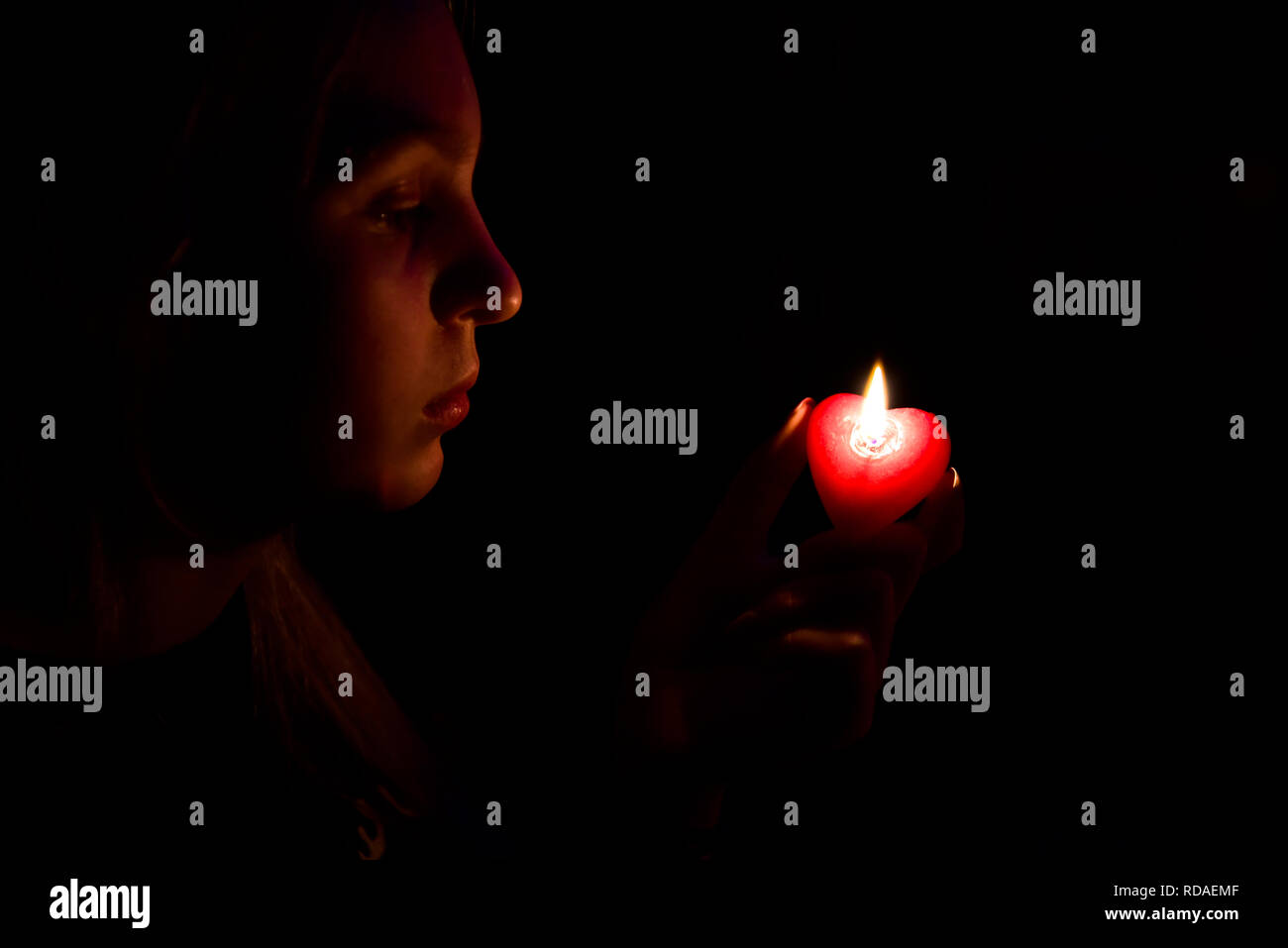 The girl in the dark looking at a lighted candle - Stock Image