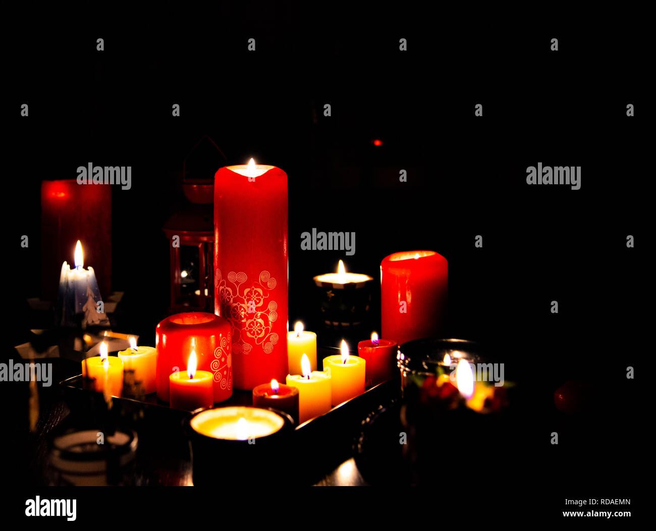 Several burning candles in the dark light - Stock Image
