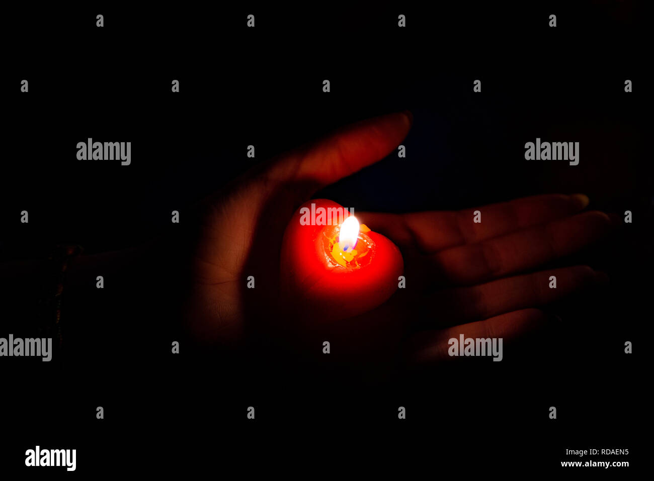 Red burning candle lying on a woman's hand - Stock Image
