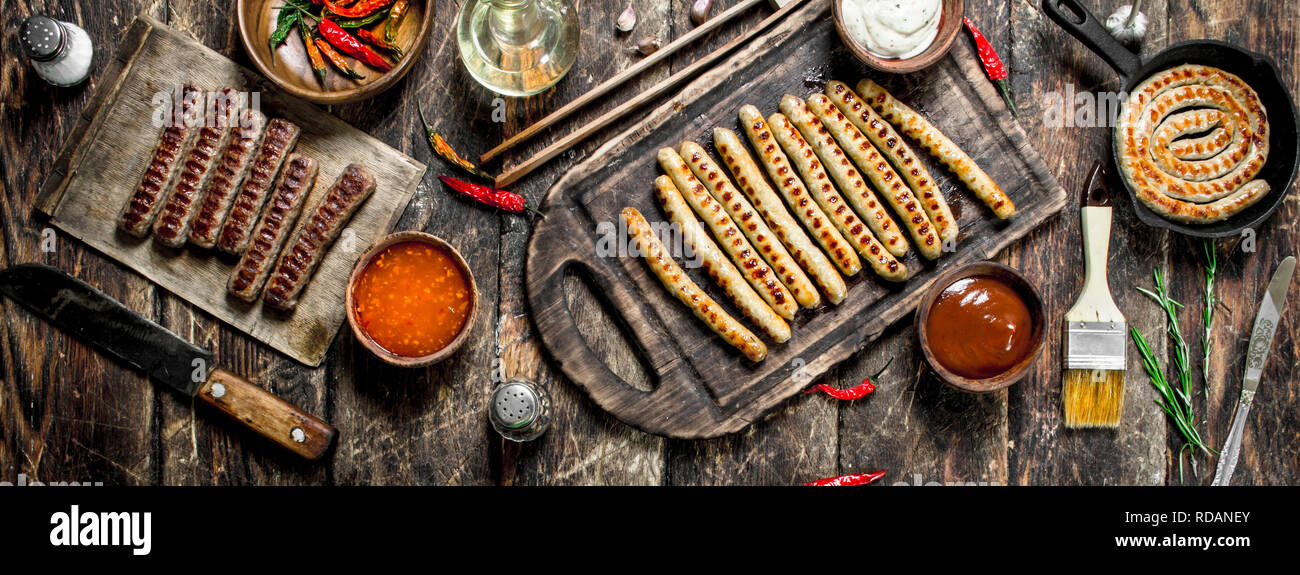 Grilled sausages with tomato sauce. On a wooden background. - Stock Image