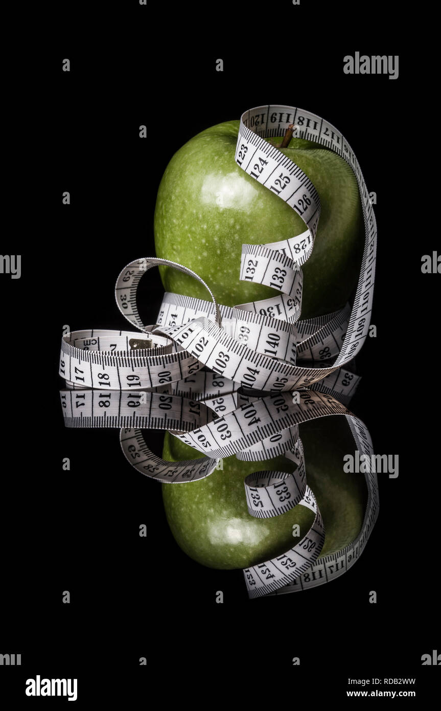 Green apple surrounded by measurement tapeline on black Stock Photo