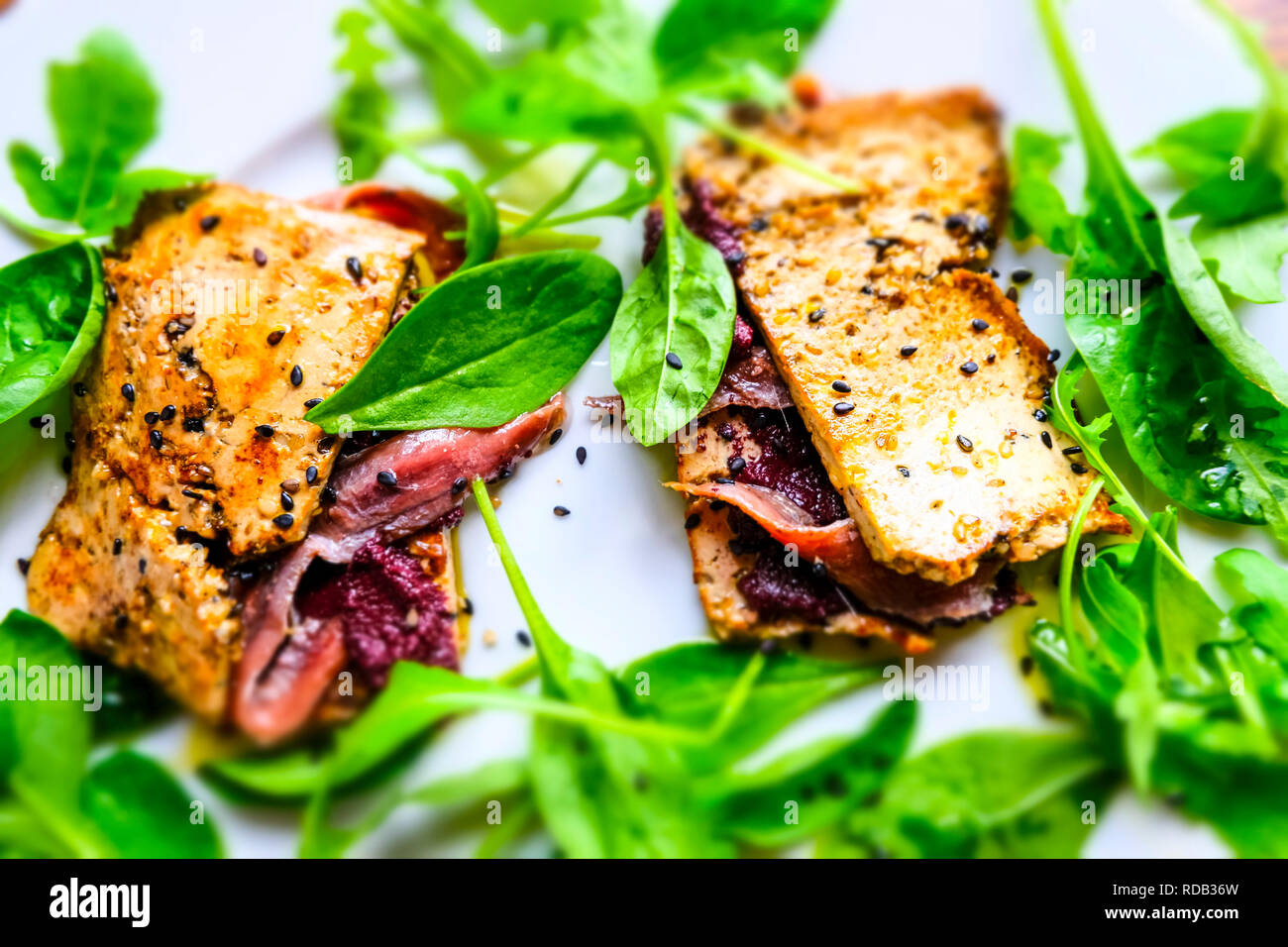 Tofu with anchovies, olive pate and corn salad. - Stock Image