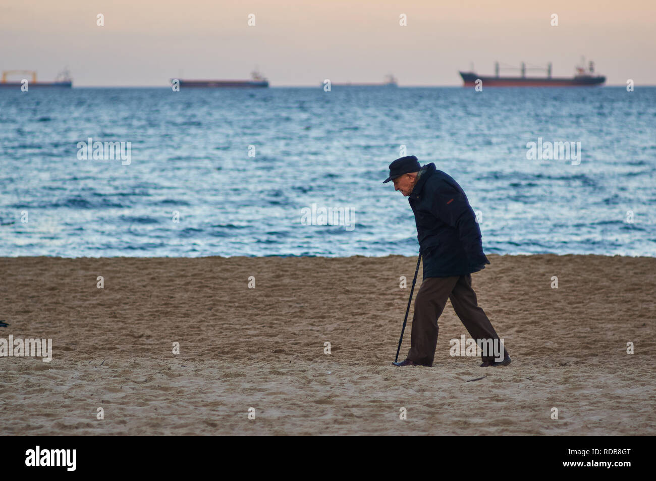 Gdansk, Poland: 26th December 2018 - An old man strolling along a Baltic sea beach with a walking stick, in winter. - Stock Image