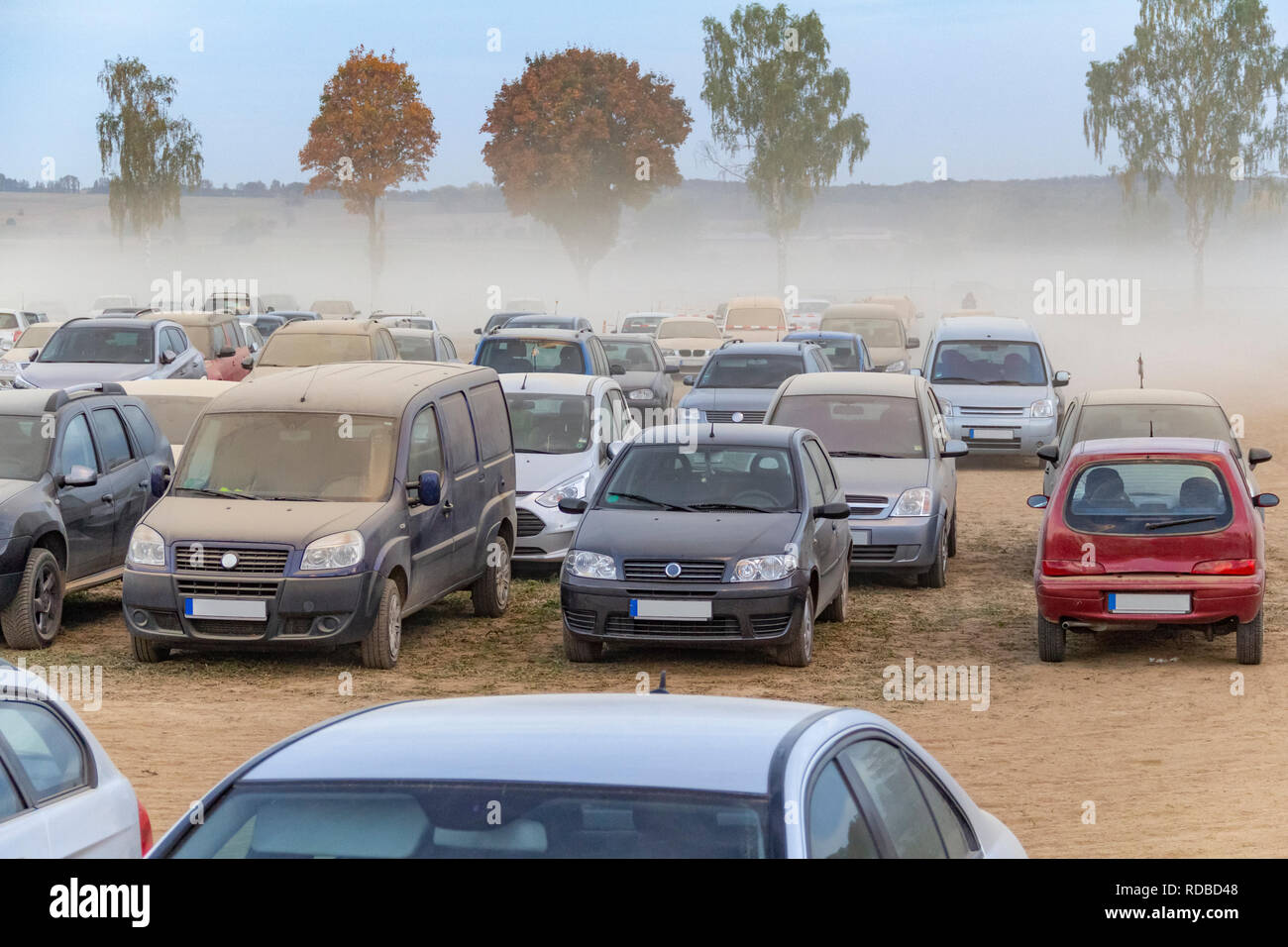 dusty parking space scenery on a field including lots of dust covered cars at evening time in Southern Germany - Stock Image