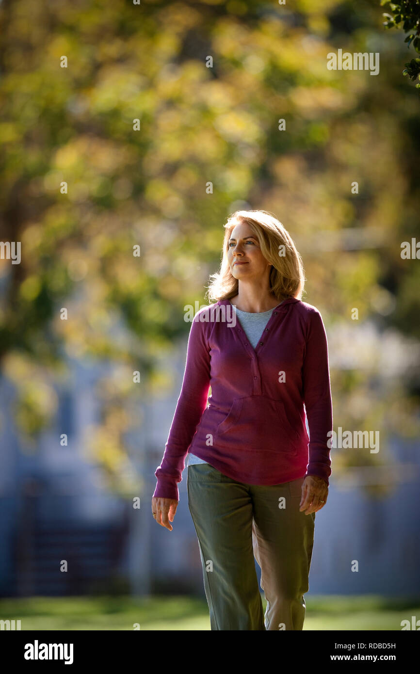Middle aged woman walking in the park. Stock Photo
