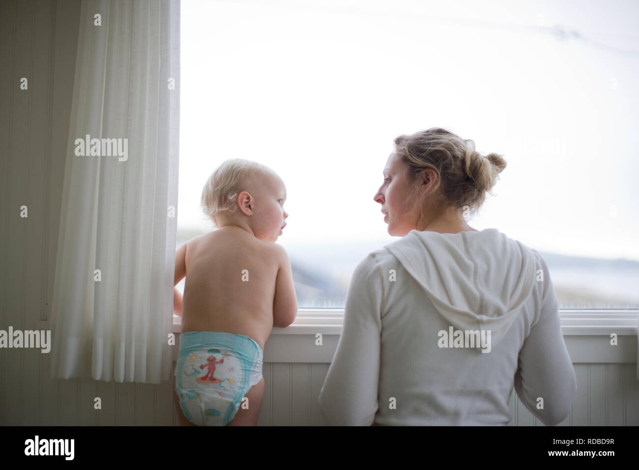 Toddler looking at his young adult mother as they look through a window. - Stock Image