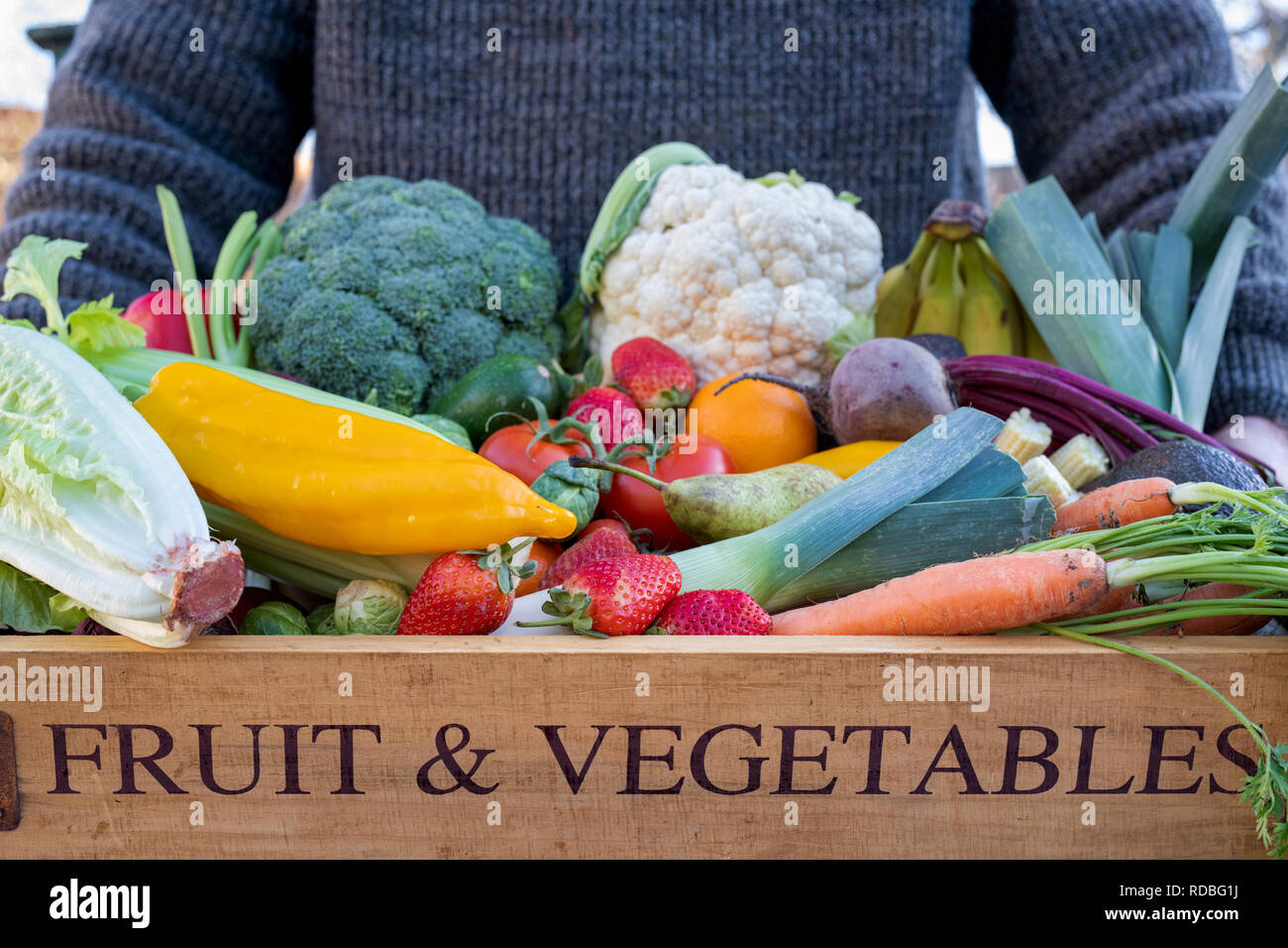 Man holding a wooden tray of fruit and vegetables. UK - Stock Image