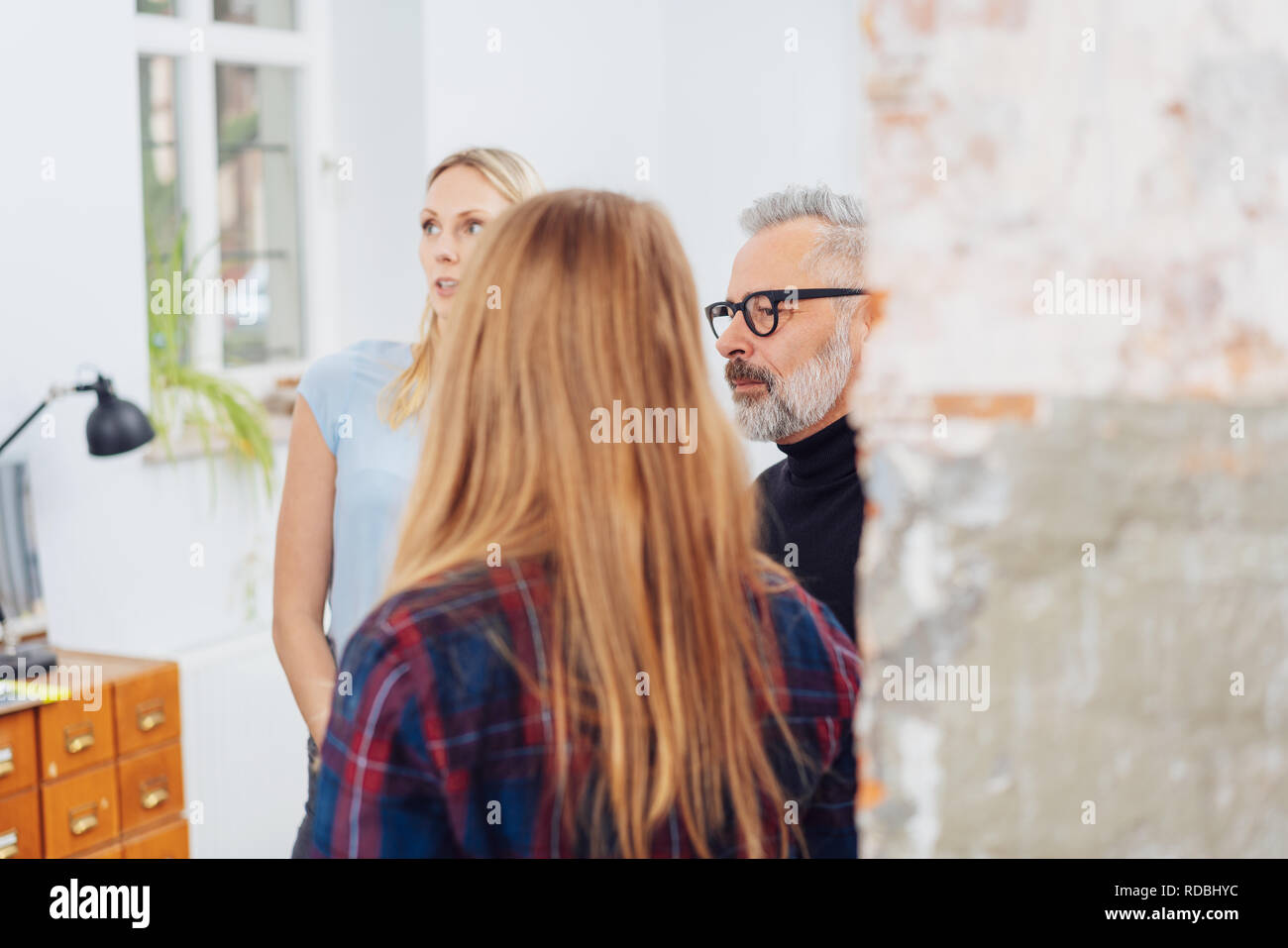 Three businesspeople standing listening with serious expressions viewed around a brick column in the office - Stock Image