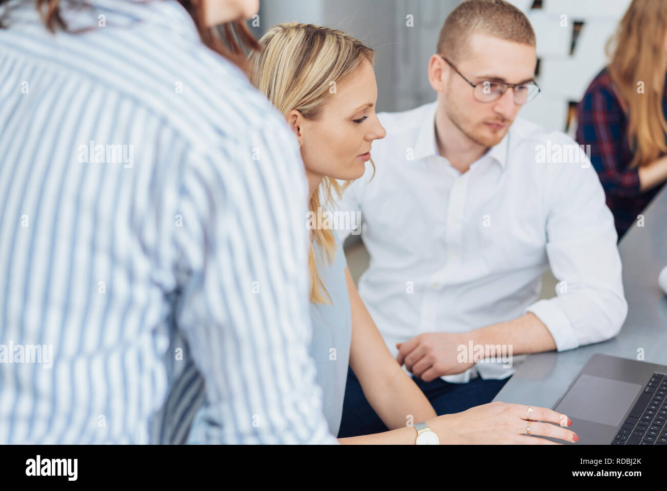 Young business team gathered around a laptop computer reading with serious expressions - Stock Image