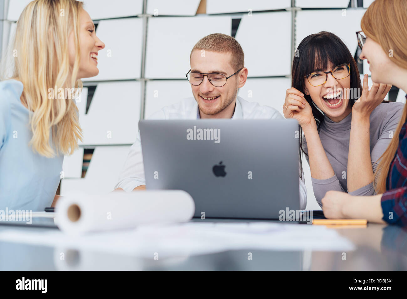 Group of young business people enjoying a joke laughing merrily while working together around an office table - Stock Image
