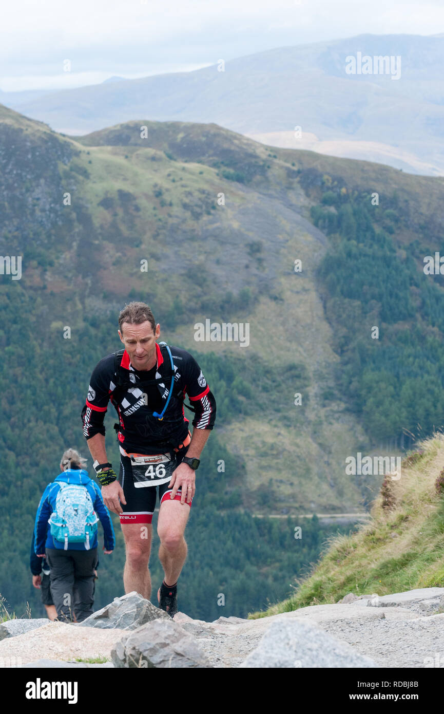 male competitor walking up Ben Nevis path during triathlon ,lochaber Scottish Highlands Scotland UK - Stock Image