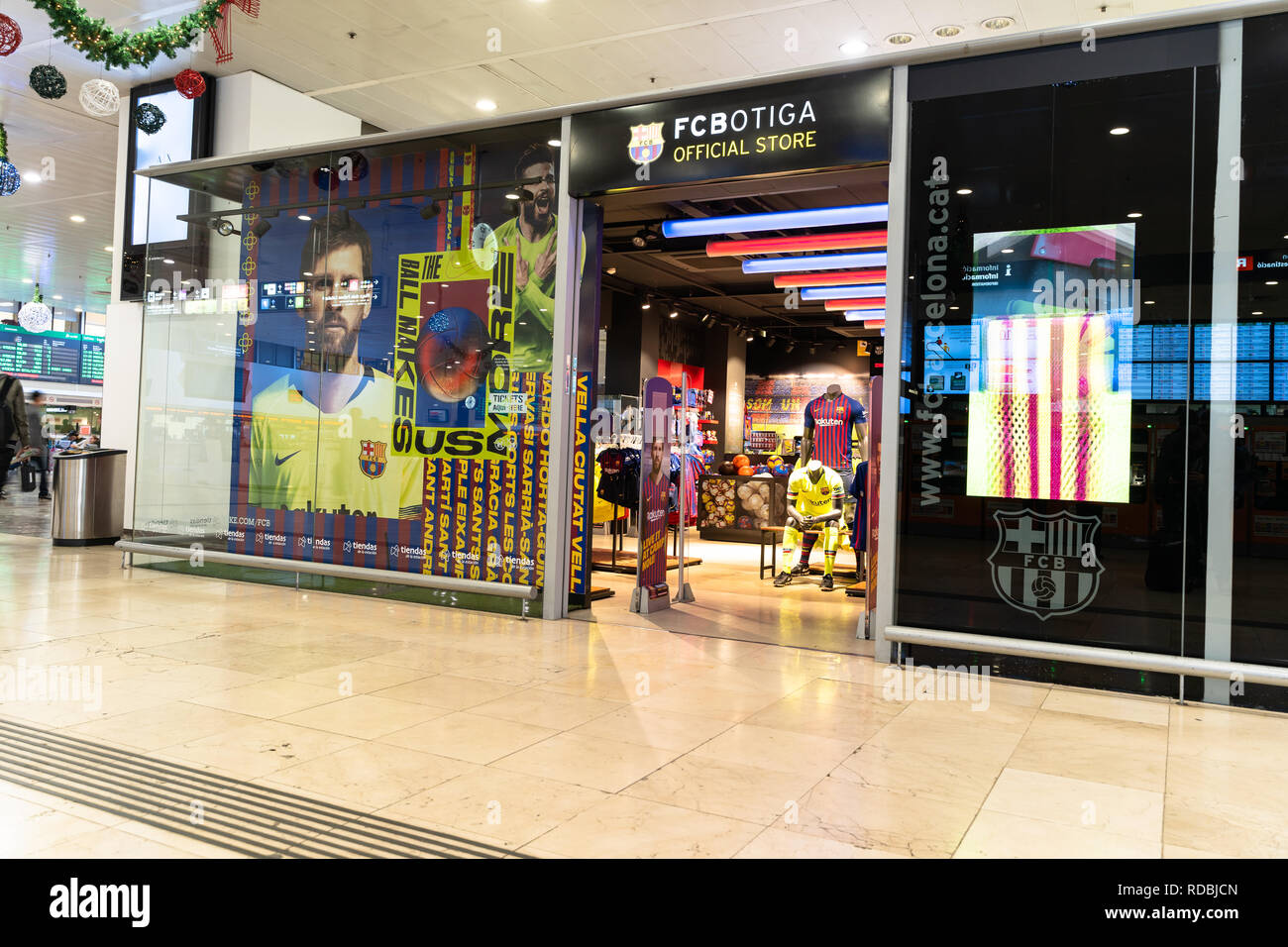 Entrance, facade to the fc botiga store of the fc barcelona footbal team with a poster by Lionel Messi in the shop window. Logo fc barcelona, Spain - Stock Image