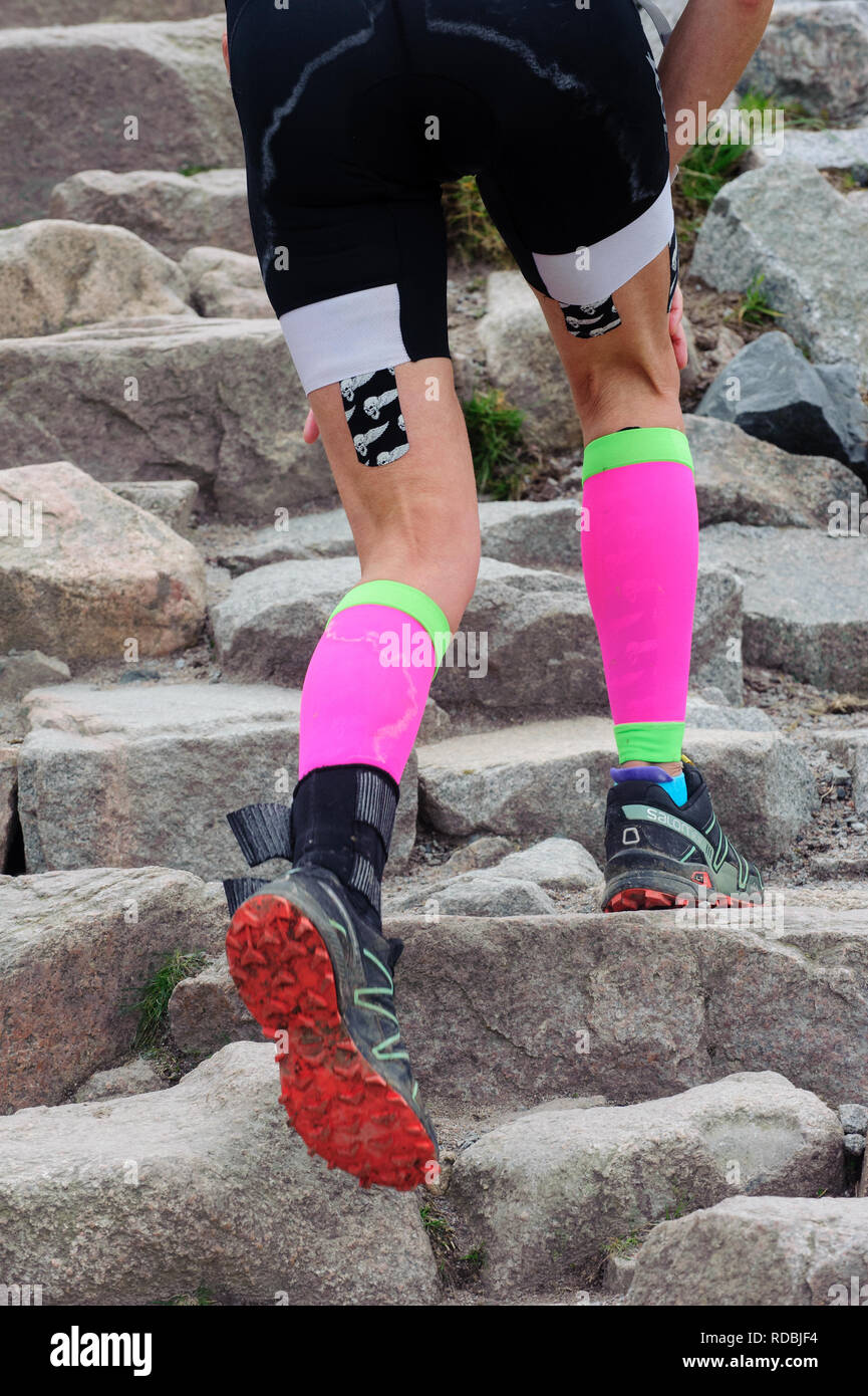 Close up of legs wearing bright clothes walking up Ben Nevis path Scotland - Stock Image