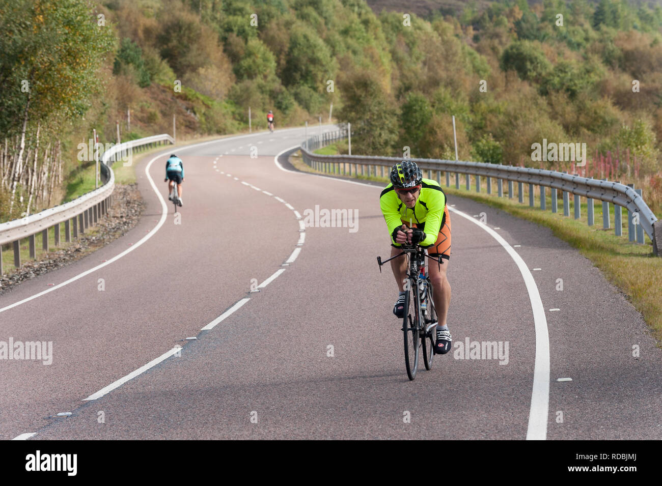 Cyclist on the A86 passing loch laggan Highlands Scotland - Stock Image
