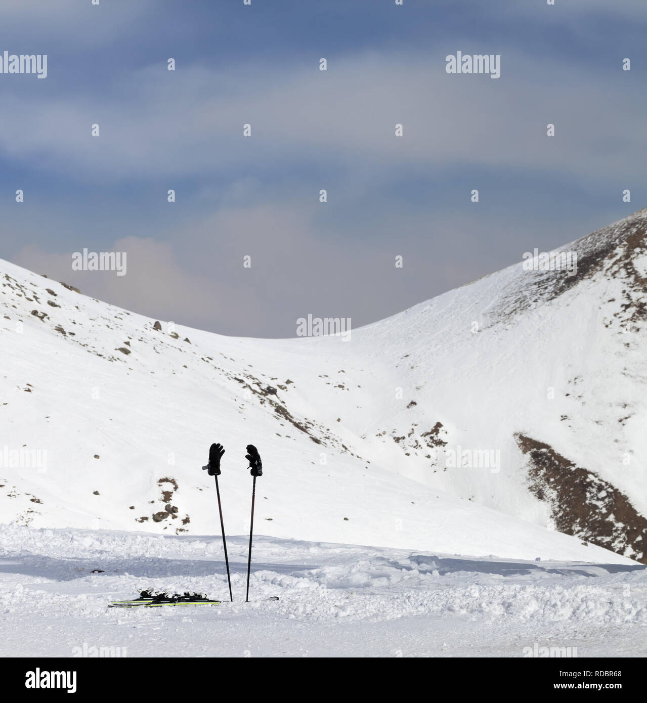 Skiing equipment on snowy ski slope at sunny winter day. Caucasus Mountains, Georgia, region Gudauri. - Stock Image