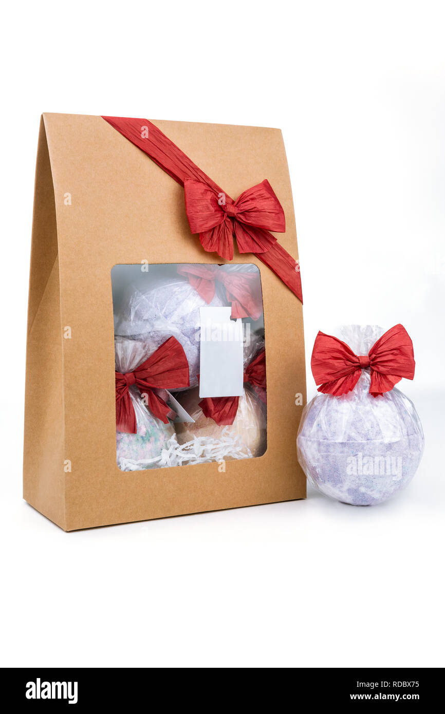 Craft Gift box decorated with red raffia bow next to bath bomb isolated on the white background - Stock Image