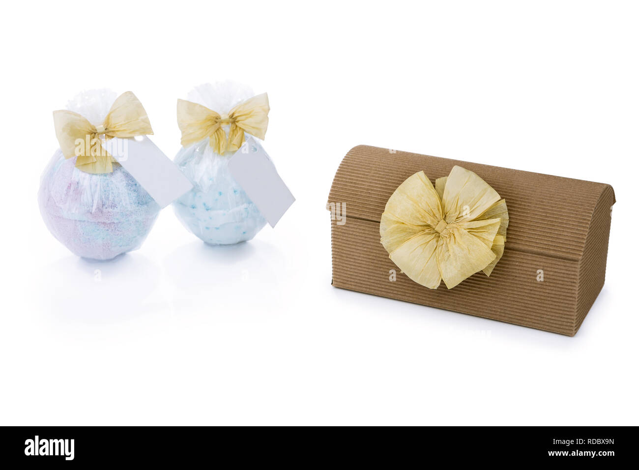 Craft Gift box decorated with ecru raffia bow next to two bath bombs isolated on the white background - Stock Image