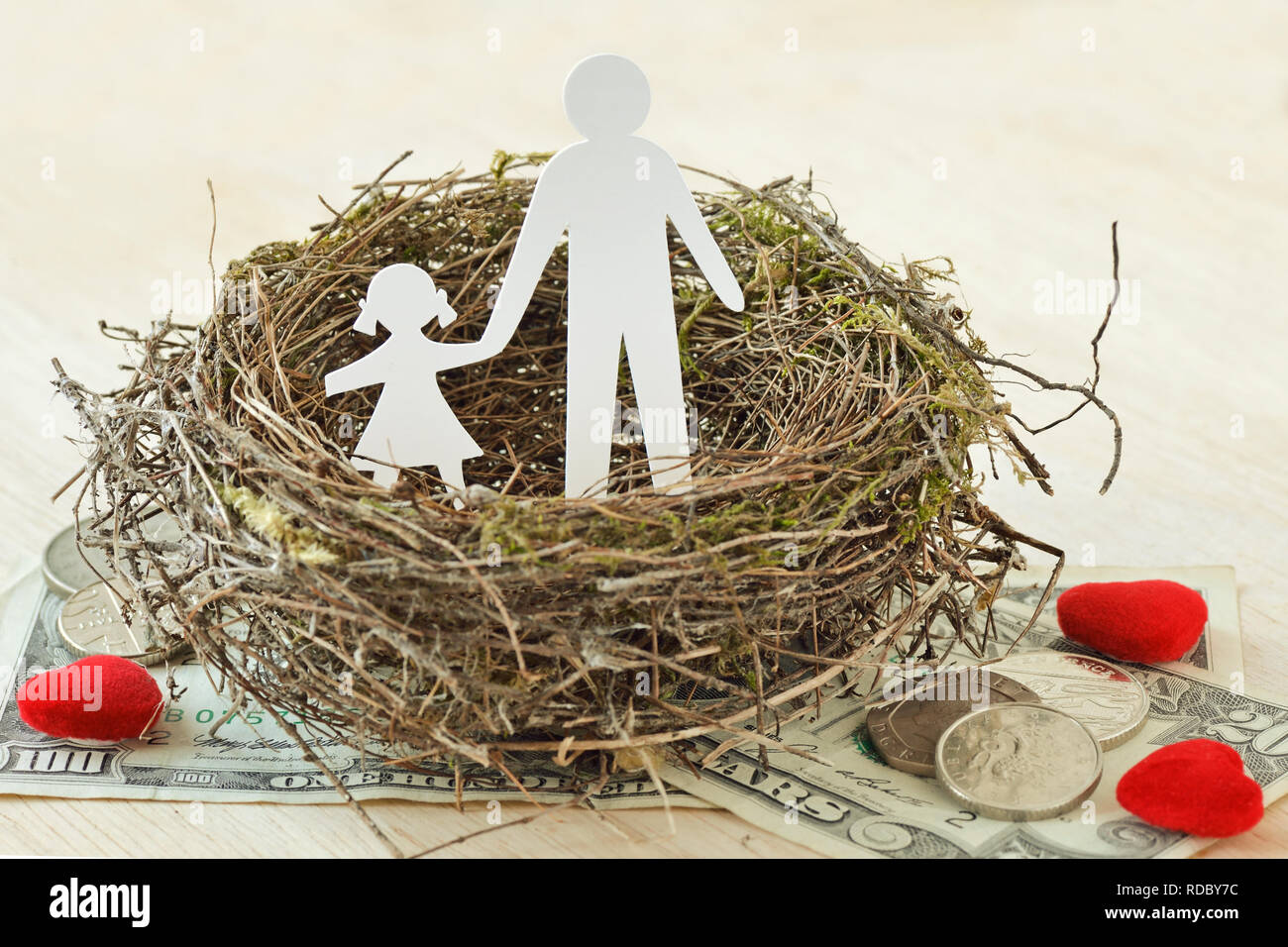 Paper father and daughter in nest on money and hearts - Concept of single parent family - Stock Image