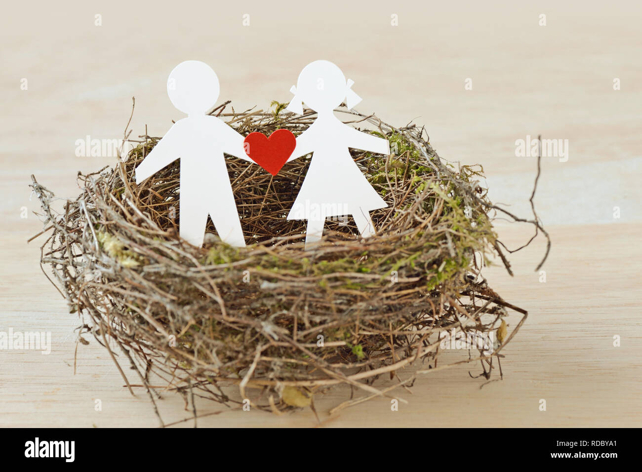 Paper children with a heart in nest - Child protection concept - Stock Image