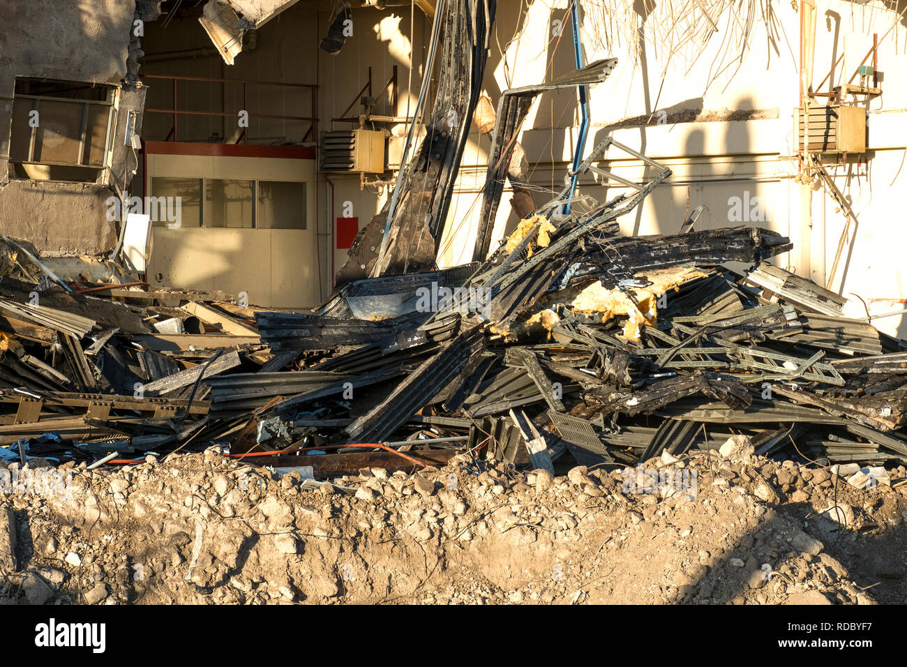 Pile of twisted and broken metal from a demolished factory background - Stock Image