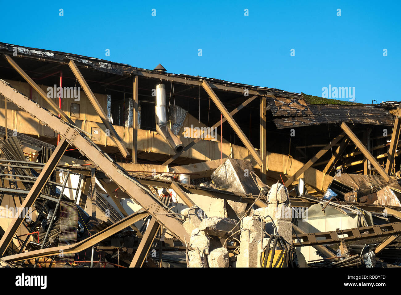 Twisted and broken metal from a demolished factory background - Stock Image