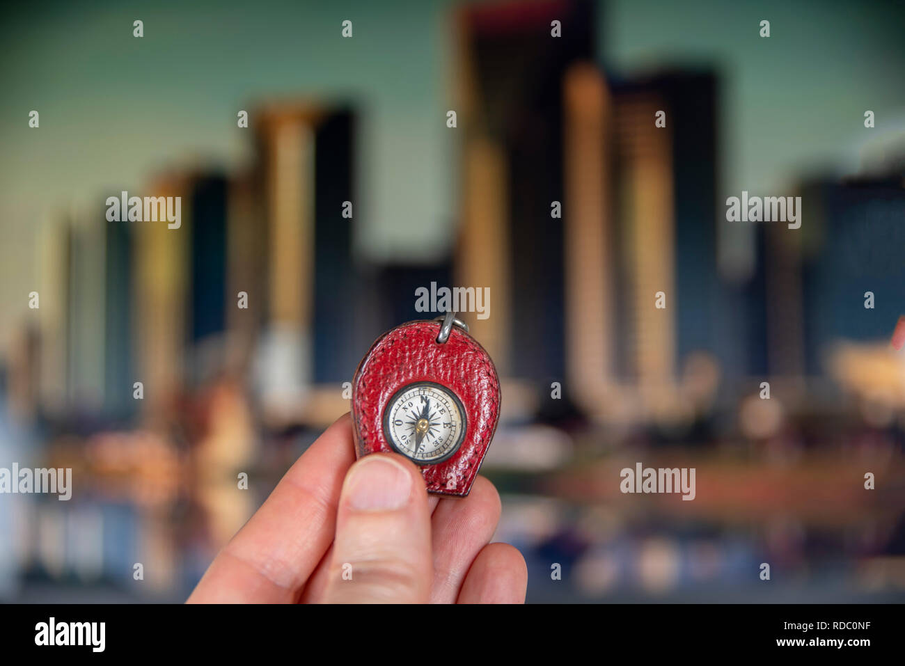 A vintage compass in one hand to navigate in a modern city - Stock Image