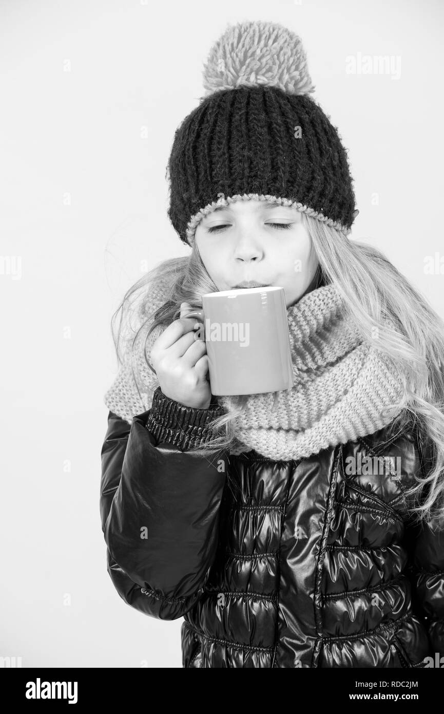 Kid in hat, pink scarf, black jacket sip tea or coffee cup on orange background. Hot drink in cold weather concept - Stock Image