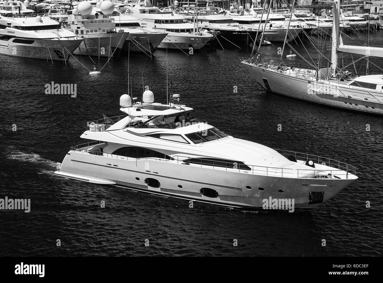 Monte Carlo, Monaco - December 08, 2009: motor yacht in navigation from port. Water craft in blue sea. Luxury lifestyle. Pleasure and sport. Summer vacation and wanderlust. - Stock Image