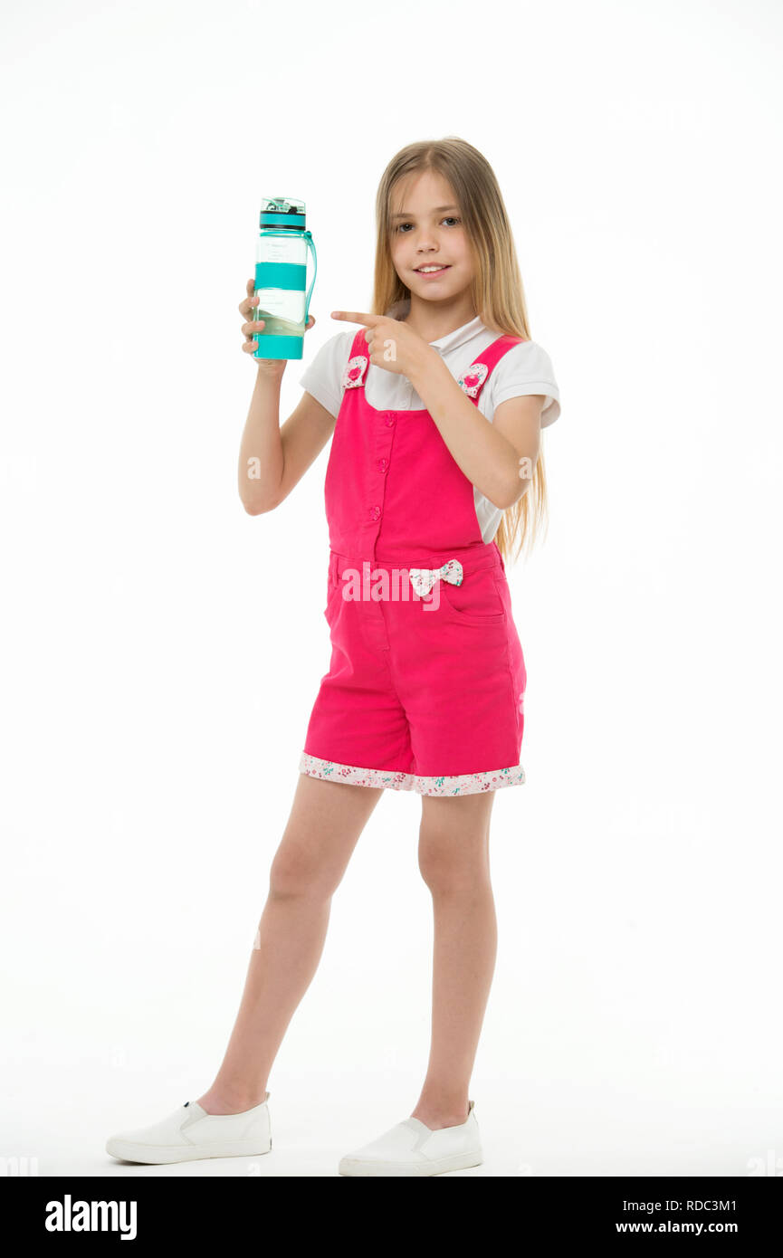 Stay hydrated. Girl cares about health and water balance. Girl on smiling face posing with water bottle isolated white background. Kid girl long hair pointing at water bottle. Water balance concept. - Stock Image