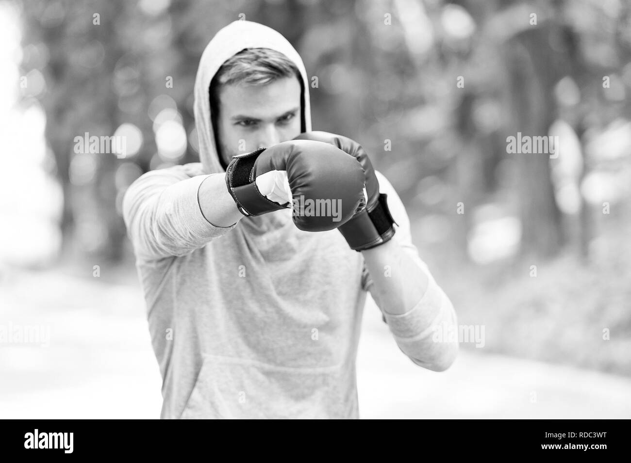 Man in boxing gloves and hood on natural landscape. Boxer exercise on fresh air. Knowckout. Man punching. Fight for success. Training his boxing skills. Born to fight. Power and energy. - Stock Image