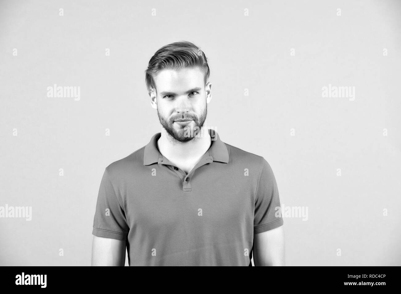 Mens beauty, fashion and style. Man in blue tshirt on grey background. Guy with bearded unshaven face. Macho with blond hair and stylish haircut. Hair care in salon or barbershop - Stock Image