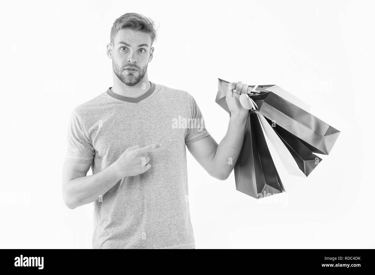 Man on surprised face pointing at shopping bags. Shopping concept. Guy holds bunch of colorful shopping bags. Man shopping on black friday. Guy bought lot items with discount. - Stock Image