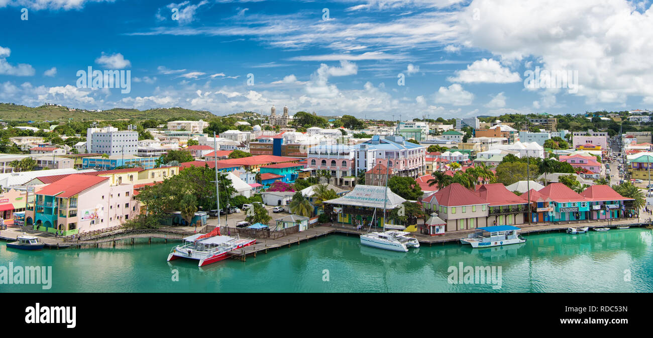 St johns, Antigua - March 05, 2016: city and sea port on cloudy blue sky. Summer vacation on tropical island. Travelling and wanderlust. Stock Photo