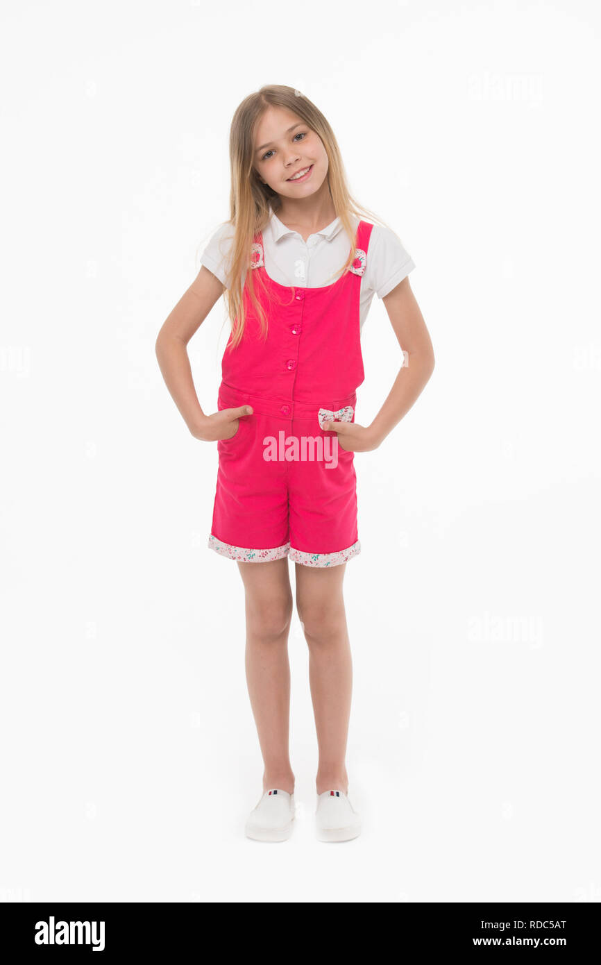 Girl wearing hot pink jumpsuit, white blouse and shoes. Cheerful kid in summer outfit, vacation concept. Child holding hands in pockets. Lovely girl with long blond hair isolated on white background. - Stock Image