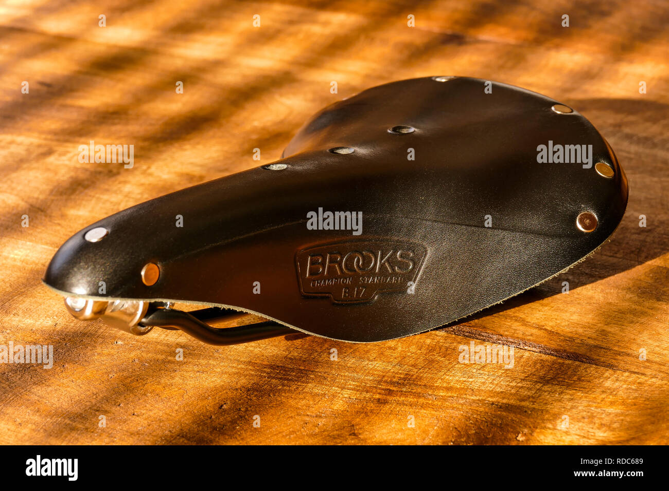 Brooks B17 standard black leather bicycle saddle on wooden table, side view Stock Photo
