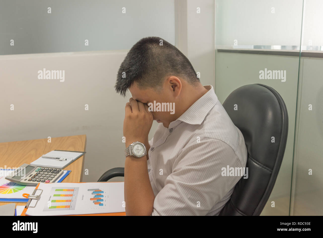 Asian manager exhausted and frustrated after checking many sales reports - Stock Image