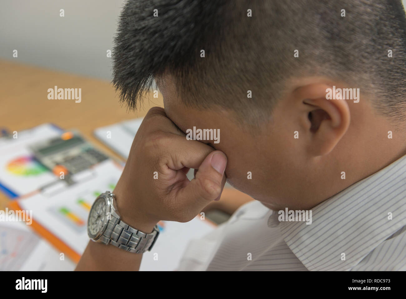 Asian businessman feel exhausted and frustrated in the office - Stock Image