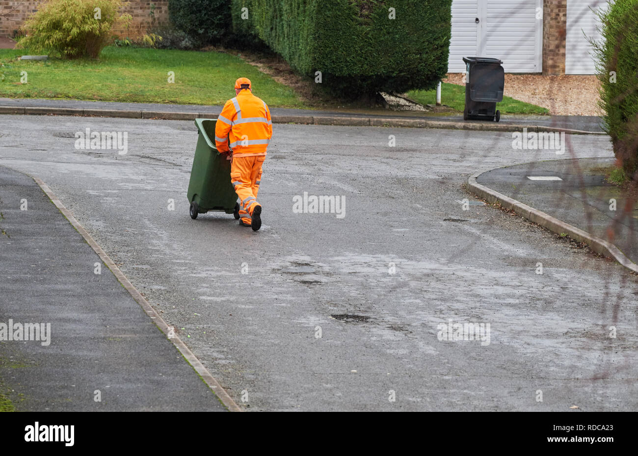 A bin man dressed in an orange fluorescent jacket and trousers pushes a green recycle wheelie bin with recyclable waste down a street on a wet winter  - Stock Image